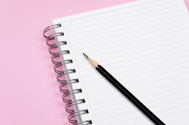 Werkruimte: kladblok en zwart potlood op roze achtergrond. minimalistische compositie.