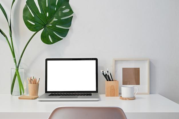 Werkruimte laptopcomputer, koffie, potlood, fotolijst en plantendecoratie op tafel.