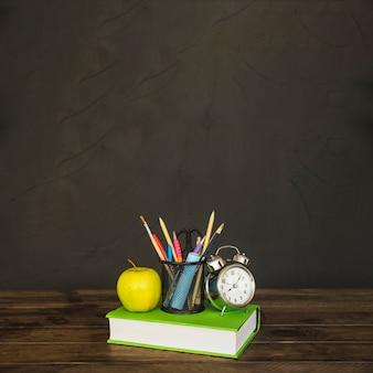 Werkruimte met boek met apple-briefpapier en wekkers