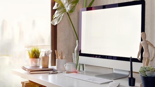 Werkruimte met een lege schermcomputer op een witte tafel
