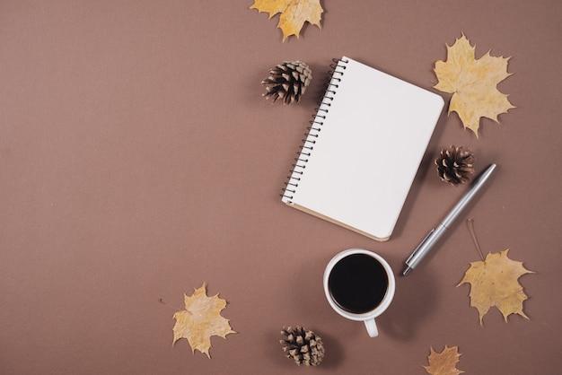 Werkruimte met gouden esdoornbladeren, koffiekopje, hobbels, notitieboekje en pen op bruine achtergrond.