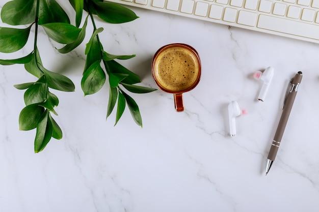 Werkruimte met kantoorbenodigdheden en gadgets draadloze hoofdtelefoon met notitieblok, pen kopje koffie