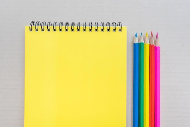 Werkruimte met kleurpotloden en notebook op bruine muur.