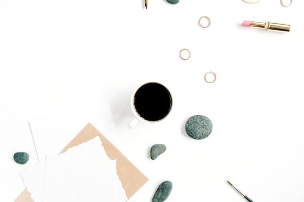 Werkruimte met koffie, ambachtelijke envelop, stenen, vrouwelijke accessoires en blanco papier op wit oppervlak