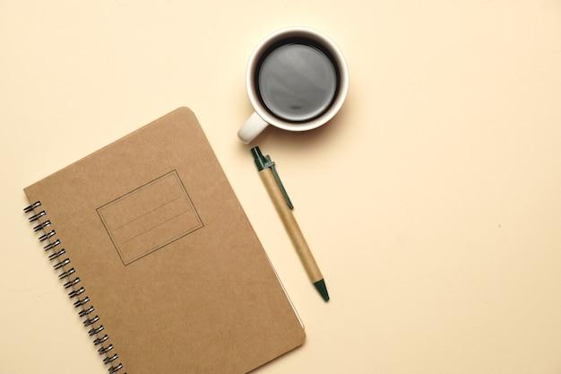 Werkruimte met koffienotitieboekje en pen op een lichtoranje achtergrond. plat liggen. plat ontwerp