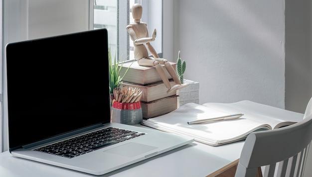 Werkruimte met laptop en benodigdheden op houten tafel in moderne kamer.