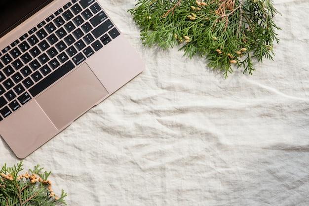 Werkruimte met laptop en schaduwen. stijlvol bureau. herfst of winter. kerstmis. plat lag, bovenaanzicht