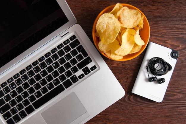 Werkruimte met laptop, flash-speler en kom chips op houten tafel. slechte gewoonten concept
