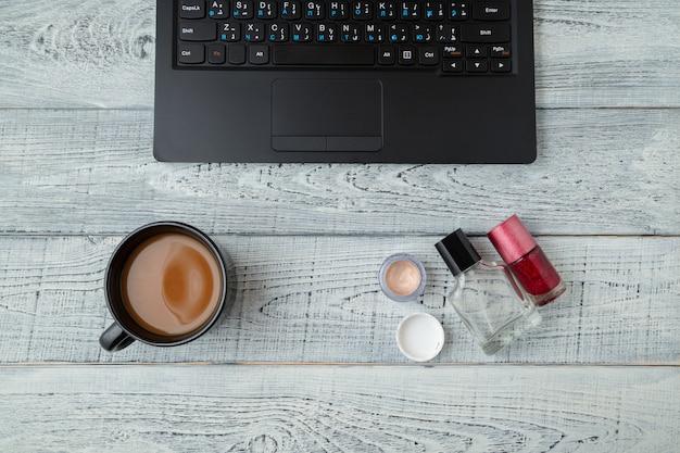 Werkruimte met laptop, koffiekopje en cosmetica op houten tafel