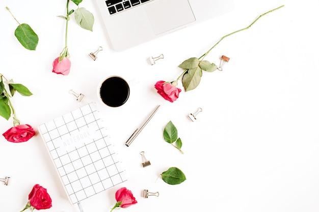 Werkruimte met laptop, rode rozenbloemen, koffiekop, notitieboekje en klemmen op wit oppervlak