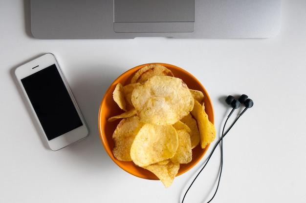Werkruimte met laptop, verfrommeld papier en kom chips op houten tafel. slechte gewoonten concept