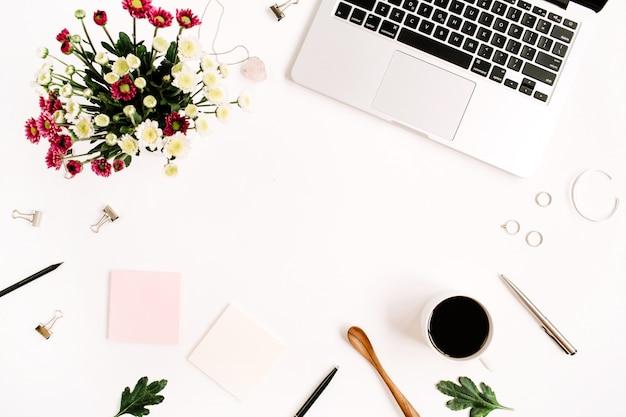 Werkruimte met laptop, wilde bloemenboeket, koffiekopje, vrouwelijke accessoires en kantoorspullen