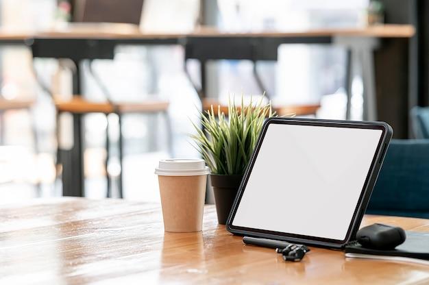 Werkruimte met leeg scherm tablet en gadget op houten tafel in co-werkruimte.