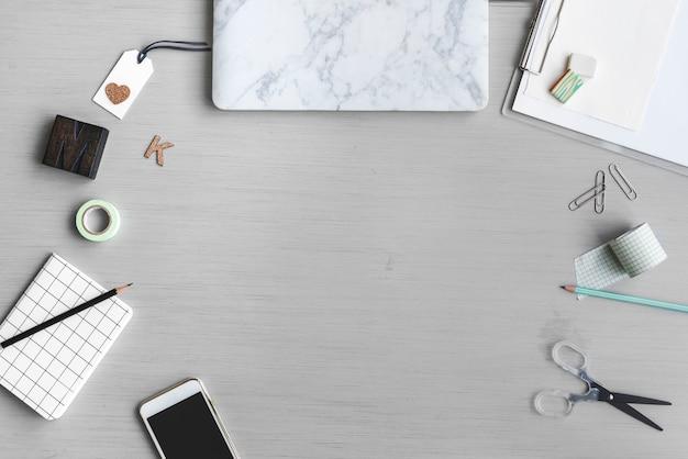 Werkruimte met notebook mobiele telefoon op grijze achtergrond