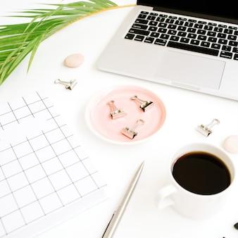 Werkruimte met notitieboekje, laptop, palmtak, koffiekopje, schaar en clips op wit