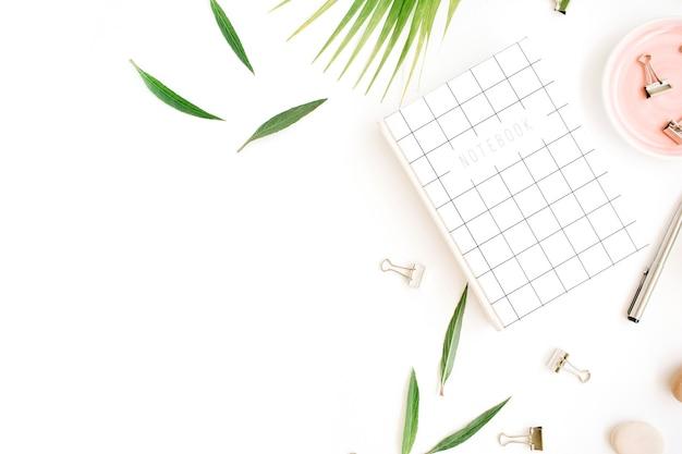 Werkruimte met notitieboekje, palmtak en clips op wit.
