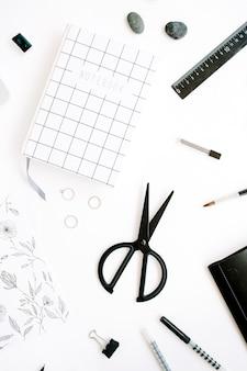 Werkruimte met notitieboekje, schaar, bril, pen op wit.