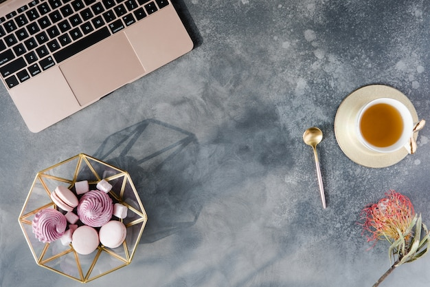 Werkruimte met pastel roze laptop, thee en decoraties op grijze achtergrond.