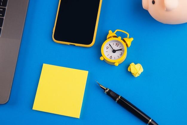 Werkruimte met pen, klok, notitie en laptop. bedrijfsfinanciën, onderwijs en exemplaarruimteconcept.