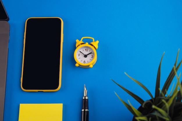 Werkruimte met pen, klok, notitie en laptop. bedrijfsfinanciën, onderwijsconcept