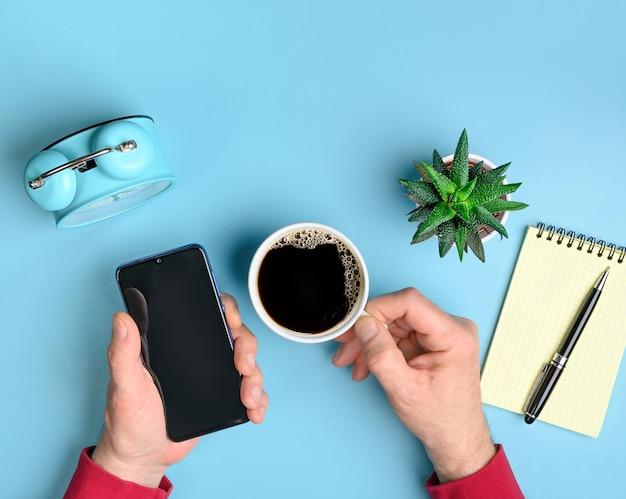 Werkruimte met smartphone en koffie in mannelijke handen op blauwe bureautafel met kopieerruimte. platliggend ontwerp.