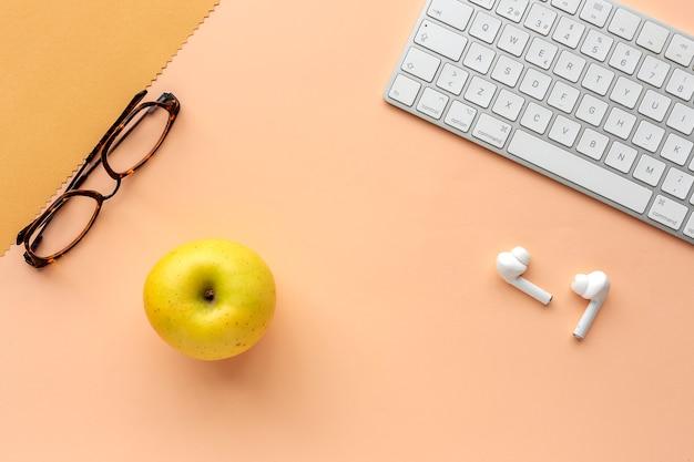 Werkruimte met toetsenbord, glazen, appel- en oordopjes