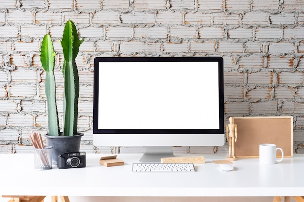 Werkruimte mockup computer met koffiemok, pot van potlood en kladblok op witte tafel