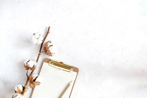 Werkruimte mockup, klembord met blanco papier, katoenen tak