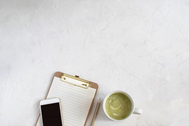 Werkruimte mockup, klembord met blanco papier, smartphone en matcha latte
