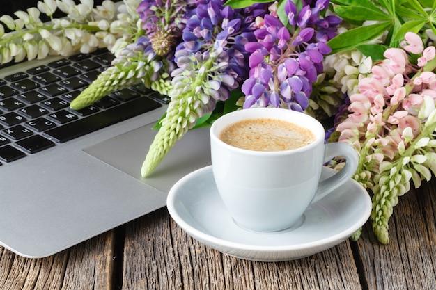 Werkruimte of werkplek met laptop, bloemen en koffie