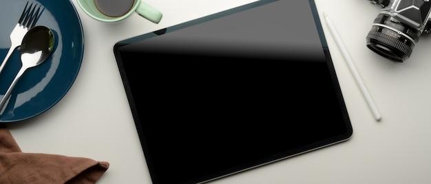 Werkruimte op eettafel met digitale tablet, camera, koffiekopje, bord, bestek en servet