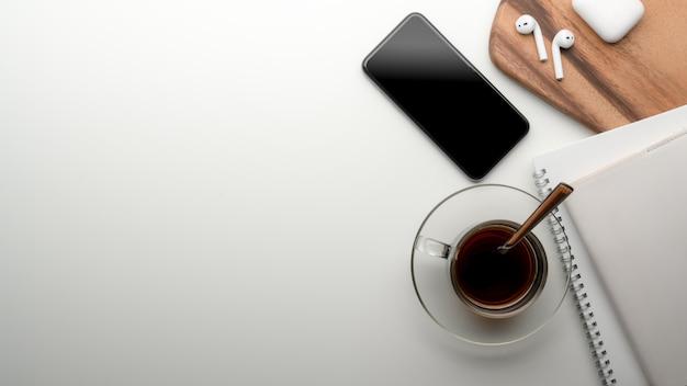 Werkruimte op eettafel met kopie ruimte, smartphone, schema boeken, theekopje, oortelefoon op houten dienblad