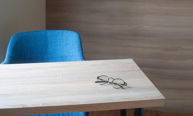 Werkruimte op houten kantoor tafel met moderne blauwe stoel in de woonkamer.