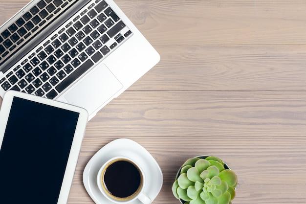 Werkruimte op kantoor, houten bureau met laptop en koffiemok bovenaanzicht
