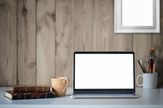 Werkruimte op zolder met mockup-laptop en kantoorbenodigdheden.