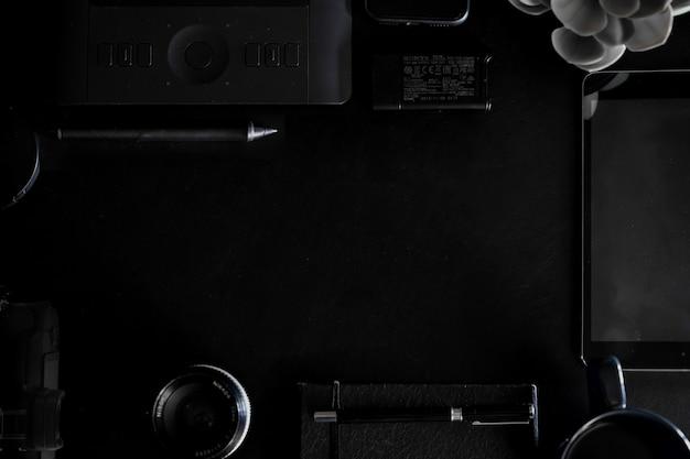 Werkruimte op zwart lederen boven tafel van een creatieve ontwerper of fotograaf en kopie ruimte