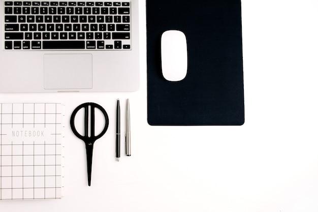 Werkruimte plat gelegd. laptop, muis, notitieboekje, pen en schaar op witte achtergrond. bovenaanzicht kantoor aan huis concept.