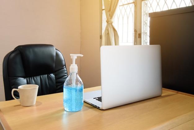 Werkruimte thuis met laptop, kopje koffie en alcoho handgel, covid-19 en thuiswerkconcept