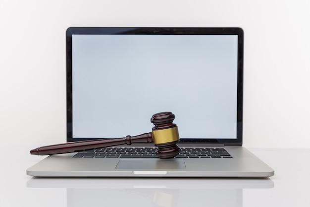 Werkruimte van advocaat met laptop leeg wit scherm en wet houten hamer, juridisch boek