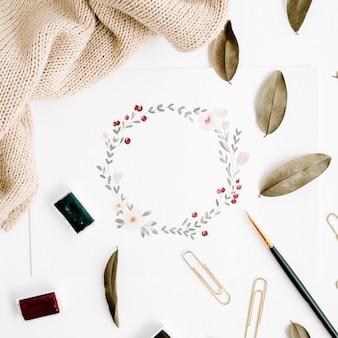 Werkruimte van de kunstenaar. bloemenkrans beschilderd met waterverf, verfborstels, gedroogde bladeren, pullover