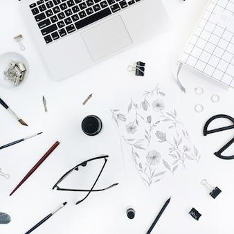 Werkruimte van de kunstenaar met schilderen, notebook, laptop, schaar, bril, pen op wit