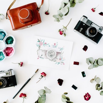 Werkruimte van de kunstenaar met vintage retro fotocamera en aquarel geschilderde camera, rode rozen en eucalyptus arrangement