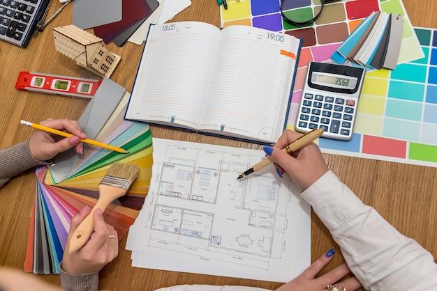 Werkruimte van de ontwerper met plattegrond en kleurenpalet, bovenaanzicht