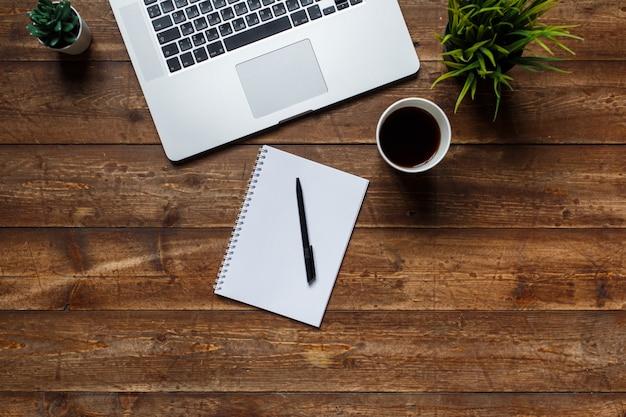 Werkruimte van een zakenman. uitzicht van boven . koffie laptop en laptop op bureaublad met zwarte notitie.