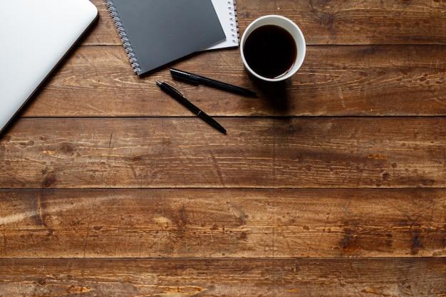 Werkruimte van een zakenman. uitzicht van boven . koffie laptop en laptop op het bureaublad met zwarte notitie.