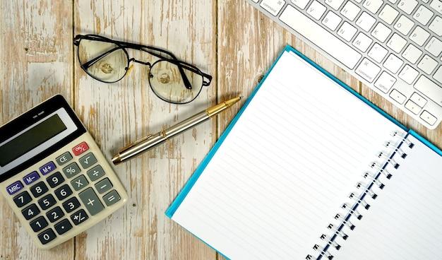 Werkruimte voor het werken met houten witte tafel met toetsenbord, rekenmachinebril en benodigdheden