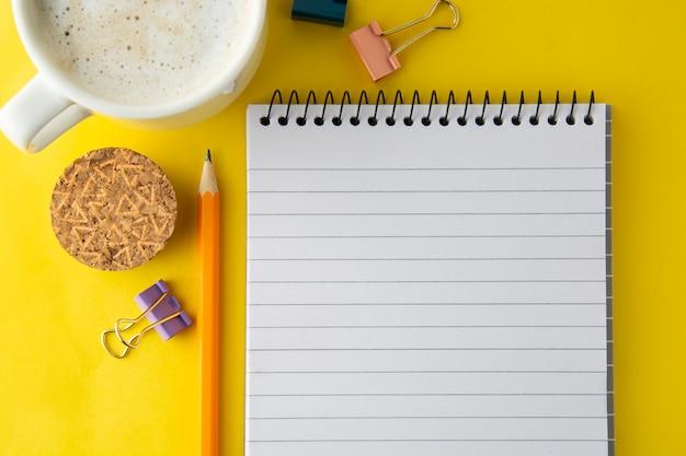 Werkruimte, werktafel. notitieblok, koffiekopje en kantoorbenodigdheden openen. plat leggen, ruimte kopiëren.