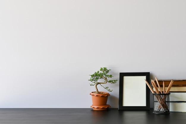 Werkruimteboeken, potlood, fotolijst en bonsai op bureau.