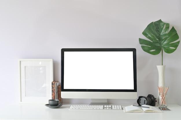 Werkruimtecomputer en bureaulevering op creatieve werkplaats met de lege vertoning van de mockuppc computer.