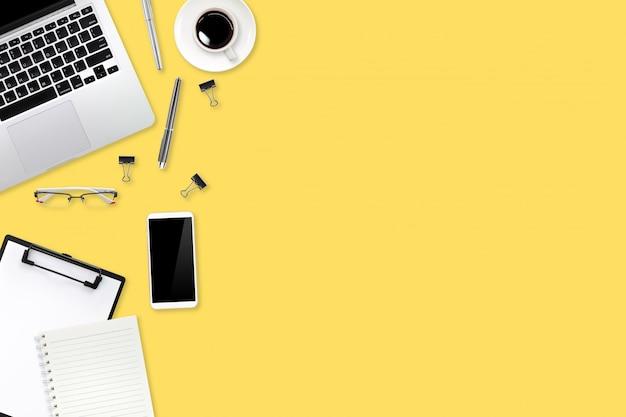 Werkruimtetafel met laptopcomputer en koffiekop op gele pastelkleurachtergrond